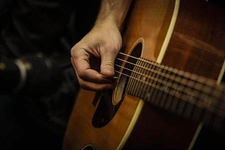 photo of person holding using pick on guitar