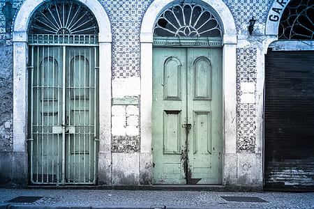 gray concrete house with green wooden doors at daytime