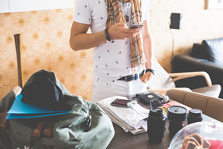 Man Checking His Phone while Packing for a Trip