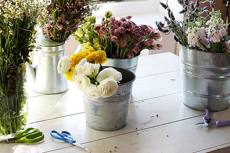 white and yellow flowers on gray metal bucket