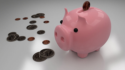 pink coin bank and assorted coins