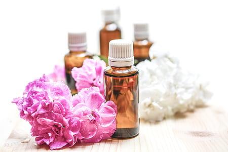 brown glass bottle beside pink flowers