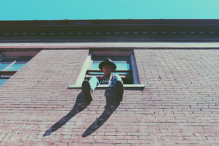 man sitting on window during daytime