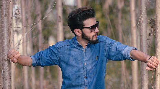 man in blue denim button-up long-sleeved shirt