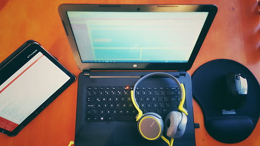 black laptop computer, wireless mouse, tablet computer, and yellow headphones on top of brown wooden furniture