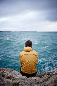 man in yellow hooded jacket sitting on cliff in front of sea
