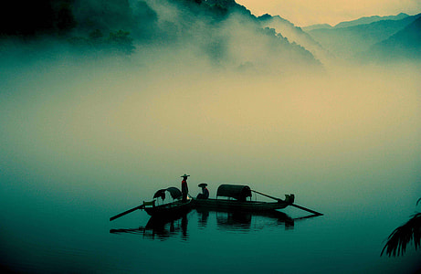 silhouette of people on wooden paddle boats on foggy lake