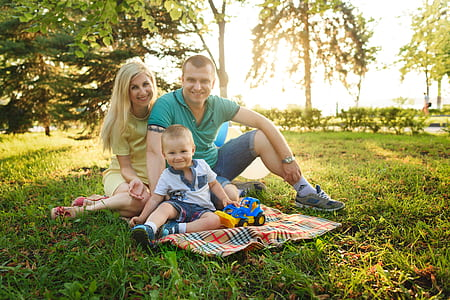 family of three sitting on the green grass