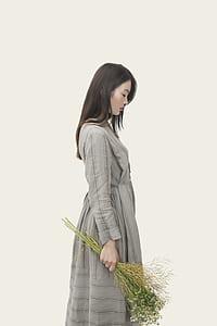 woman wearing gray long-sleeved dress holding flower