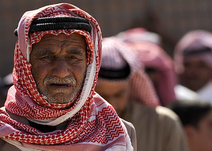 selective focus portrait photo of man in red keffiyeh with black agal headdress