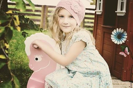 girl wearing floral dress sit on rocking horse