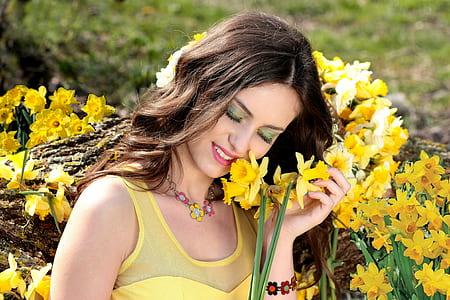 women's yellow top near yellow flowers at daytime