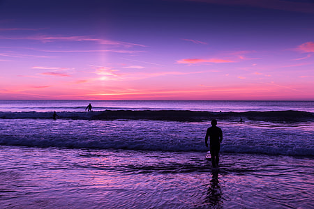 People in the ocean at sunset
