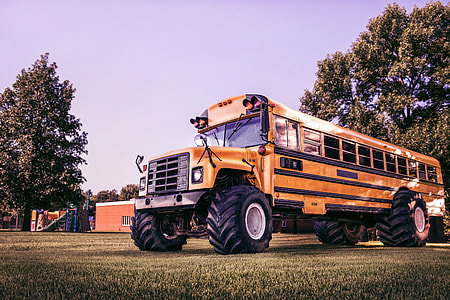 yellow school bus on grass field at daytime