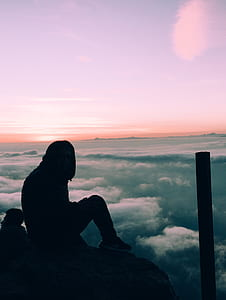 silhouette of person sitting under purple sky