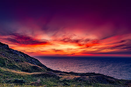 landscape photo of hill, sunset, and ocean