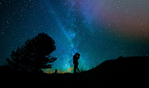 silhouette couple kissing under starry night