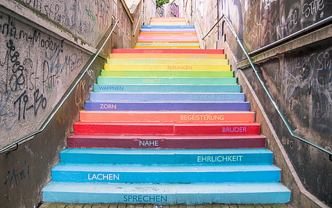 multicolored stairway with text and graffiti at daytime