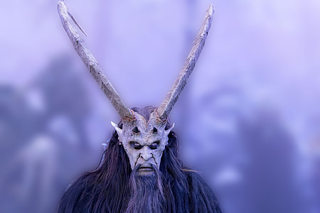 selective focus photo of person wears gray animal mask and horn