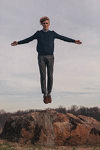 jump shot photography man in long sleeves shirt and gray pants