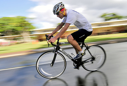 man wearing white t-shirt and black shorts on bike in time laps photography