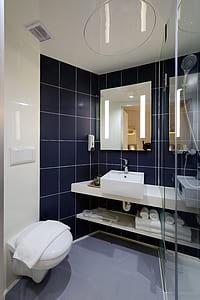 white toilet bowl near wash basin