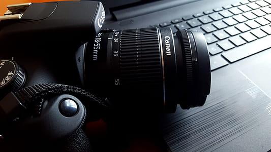 black Canon DSLR camera on black laptop