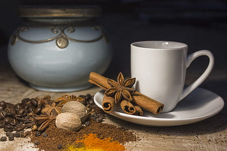 white ceramic teacup with saucer with four brown cinnamon rolls and star anise