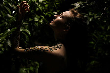 Woman with tattoos in plant foliage
