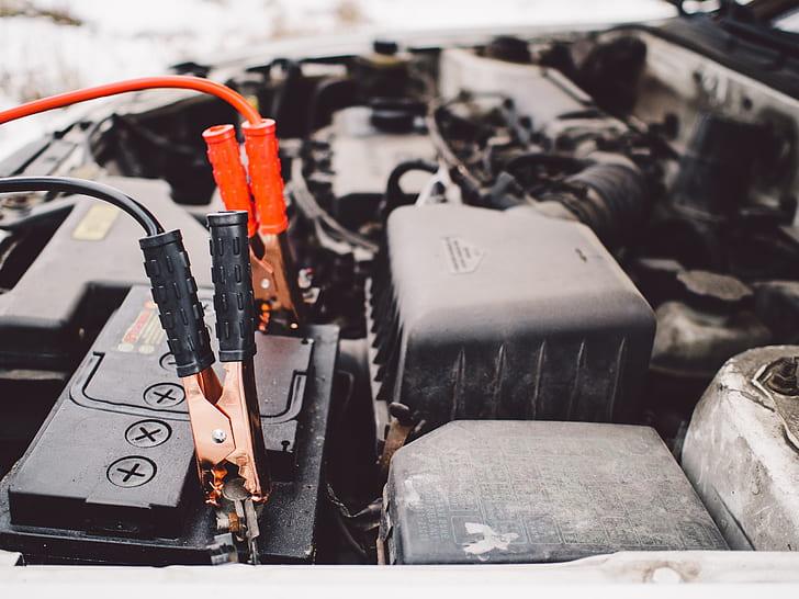 black vehicle engine with alligator clips on vehicle battery