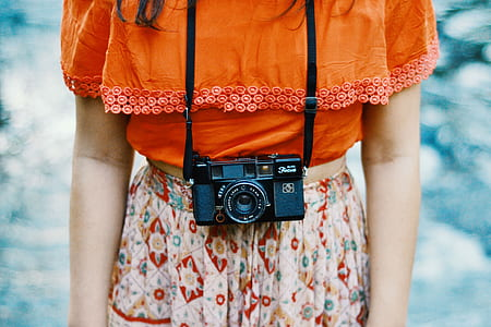 woman in orange top and white floral bottoms with black compact film camera