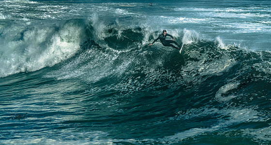 man in black wetsuit surfing on big wave during daytime