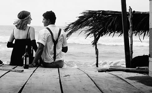grayscale photo of couple sitting on wooden surface near seashore at daytime