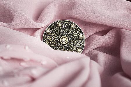 round bronze button on pink textile