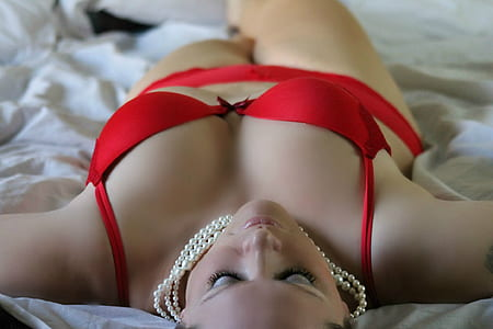 woman in red bra and panty lying on white covered bed