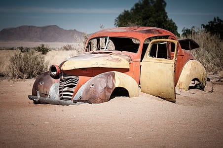 photo of vintage red car on brown sand