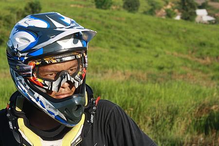 Man Wearing White Blue and Black Motorcycle Helmet during Daytime