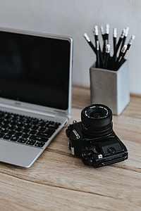 Black-and-white photos with a silver laptop, a smartphone, car keys, pencils and a camera