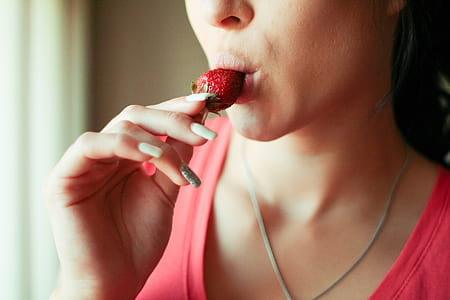 woman with strawberry in mouth