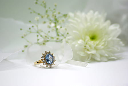 gold-colored blue stone encrusted ring beside white flower
