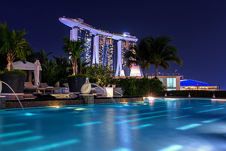 swimming pool near high-rise building during nighttime