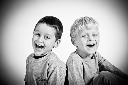 two boys smiling grayscale photography