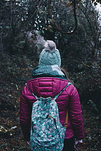 girl wearing coat and blue backpack
