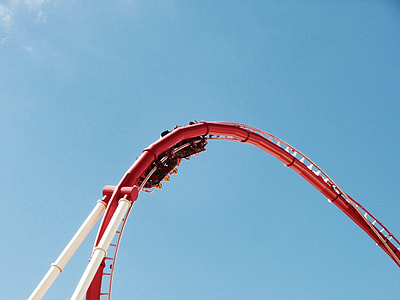 people riding on roller coaster under blue calm sky