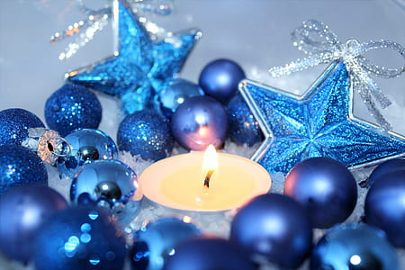 blue Baubles near yellow candle