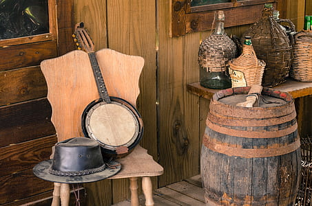 cowboy hat and string instrument on chair beside wine barrel