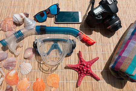 teal and red snorkeling goggles with DSLR camera and sea shells photography during daytime