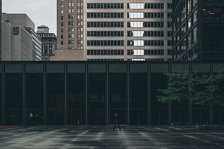 man walking beside gray building