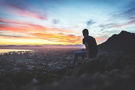 man sitting on hill with cityscape view