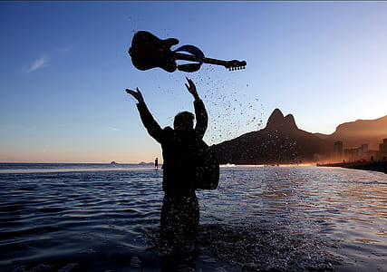 person in water throwing guitar